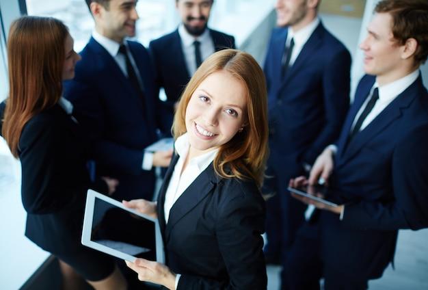 Executivo elegante com colegas de trabalho de fundo