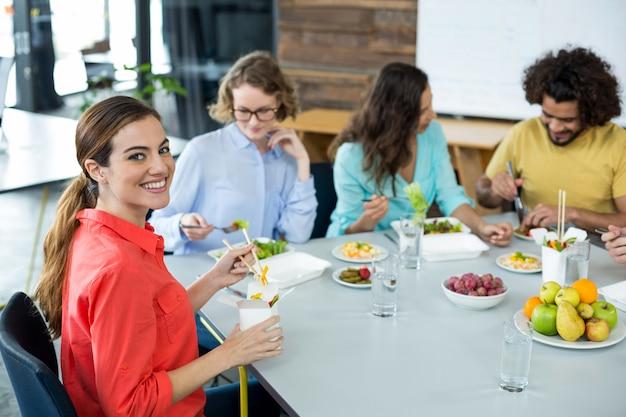 Executivo empresarial de sorriso que tem a refeição no escritório