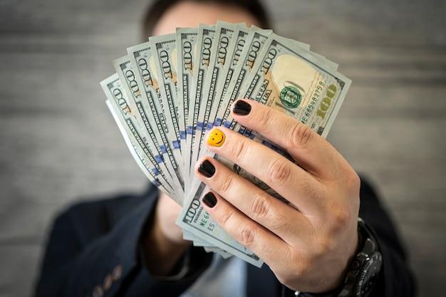 Executivo empresarial em um terno formal, dando dinheiro como suborno. um jovem com lindas unhas pintadas na moda segura dinheiro, dólares, dólares nas mãos
