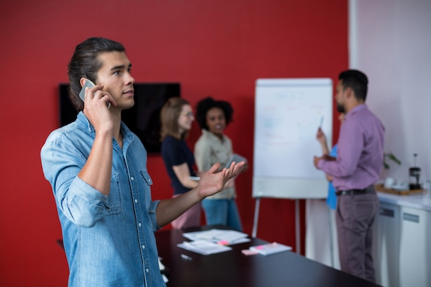 Executivo empresarial falando no telefone móvel na reunião