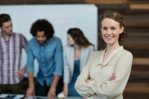 Executivo empresarial feminino sorridente em pé com os braços cruzados no escritório