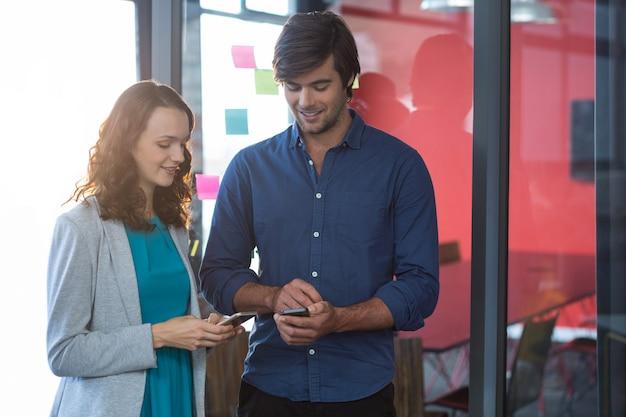 Executivo empresarial masculino e feminino, usando telefone celular