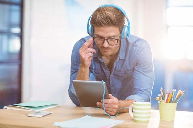 Executivo empresarial, ouvindo música no tablet digital