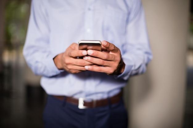 Executivo empresarial, segurando o telefone móvel