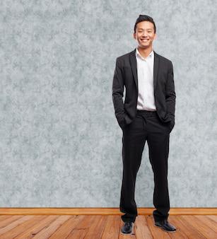 Executivo feliz com uma camisa branca e as mãos nos bolsos