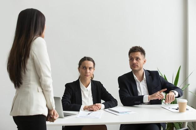 Executivo irritado apontando para o empregado de bronca de relógio de pulso por estar atrasado