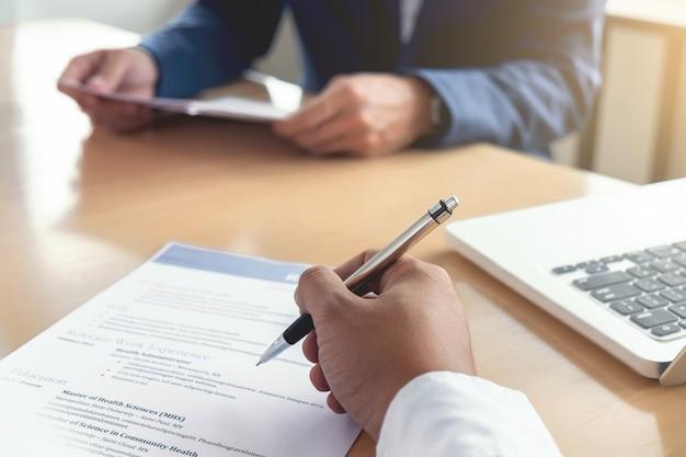 Executivo lendo um currículo durante uma entrevista de emprego e empresário completando o aplicativo f
