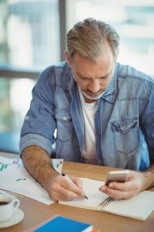Executivo masculino escrevendo no organizador enquanto usa o telefone celular