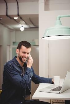 Executivo masculino falando no celular enquanto toma um café no escritório