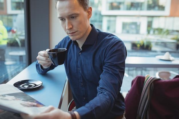 Executivo masculino lendo jornal enquanto toma café