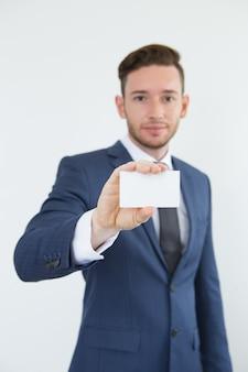 Executivo masculino moderno que mostra o cartão em branco