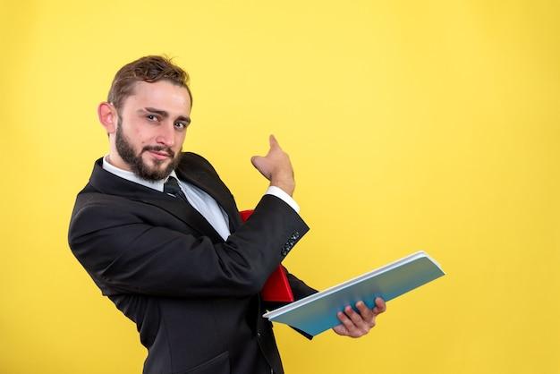 Executivo masculino mostrando algo com o dedo no lado esquerdo segurando o documento