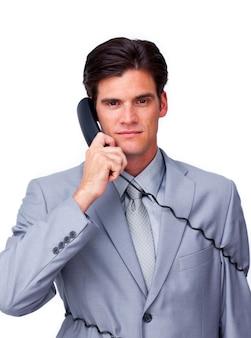 Executivo masculino sério emaranhado em fios de telefone
