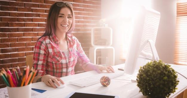 Executivo sorridente usando computador desktop no escritório