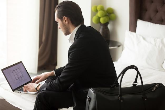 Executivo verifica plano imobiliário no laptop no hotel