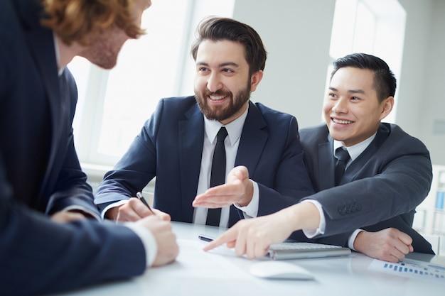 Executivos amigáveis apontando para um relatório