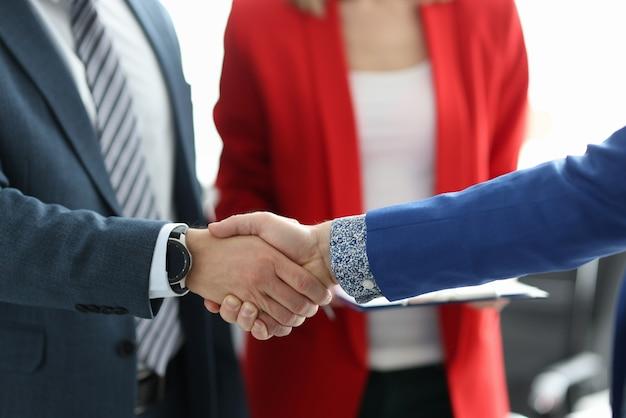 Executivos apertando as mãos em close do escritório