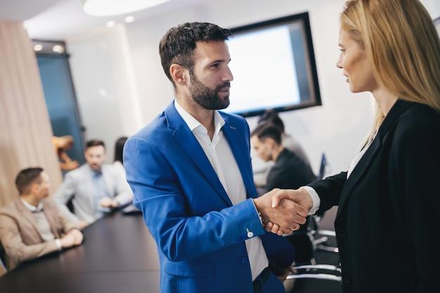 Executivos apertando as mãos em uma moderna sala de conferências