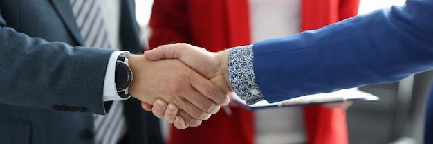 Executivos apertando as mãos no conceito de parcerias de negócios de close up de escritório
