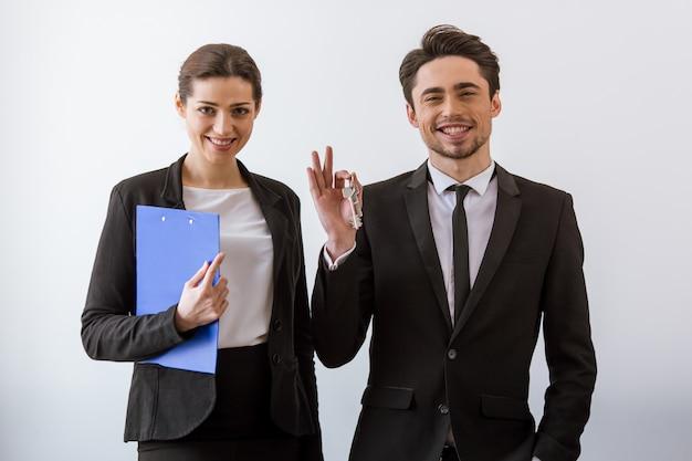 Executivos atrativos em ternos clássicos que sorriem.