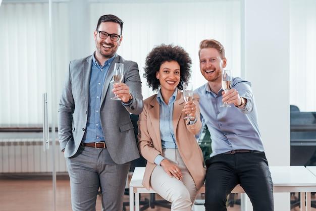 Executivos atrativos felizes que guardam o vidro do champanhe.