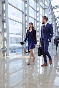 Executivos caminhando em um moderno corredor de vidro