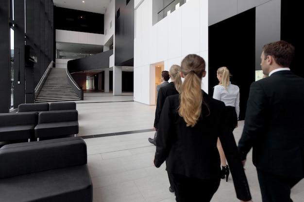 Executivos caminhando no saguão de um edifício moderno