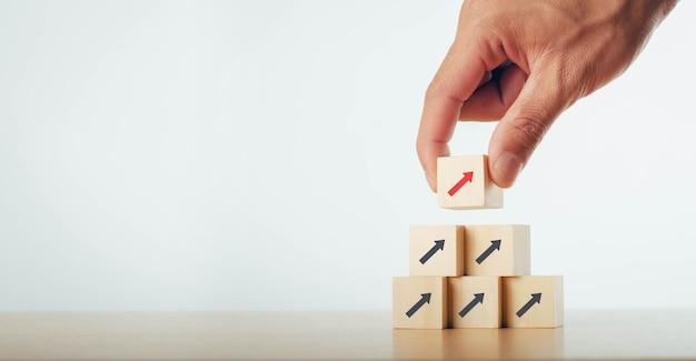 Executivos com a mão empilhados blocos de madeira em estágios conceito de negócio de inicialização seta para cima ideia de processo de crescimento de negócios de sucesso