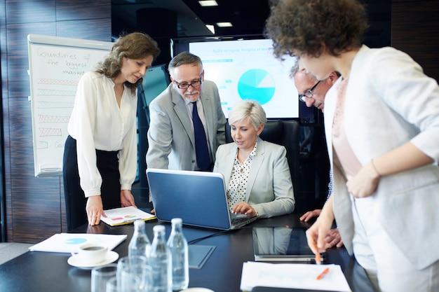 Executivos com relatório trabalhando em laptop