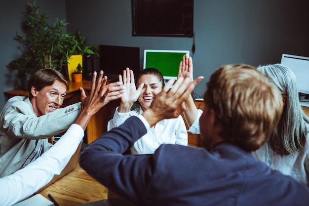 Executivos dando cumprimentos uns aos outros e batendo palmas. equipe de negócios comemorando o sucesso.