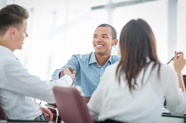 Executivos de aperto de mão sentados em uma mesa