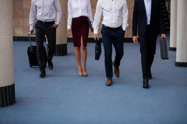 Executivos de negócios andando em um lobby de centro de conferências