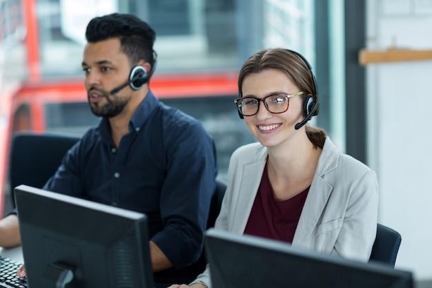 Executivos de negócios com fones de ouvido usando computadores na mesa no escritório