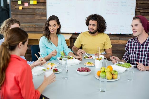 Executivos de negócios com refeição no escritório a sorrir