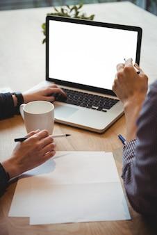 Executivos de negócios, discutindo sobre laptop