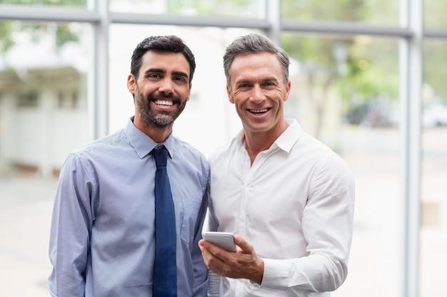 Executivos de negócios felizes segurando o telefone móvel
