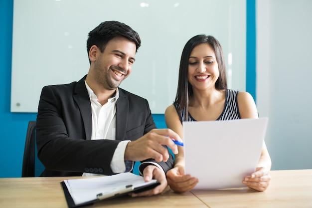 Executivos de negócios positivos rindo durante a leitura de contrato