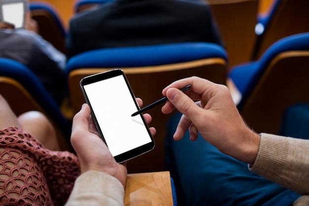 Executivos de negócios que participam de uma reunião de negócios usando telefone celular
