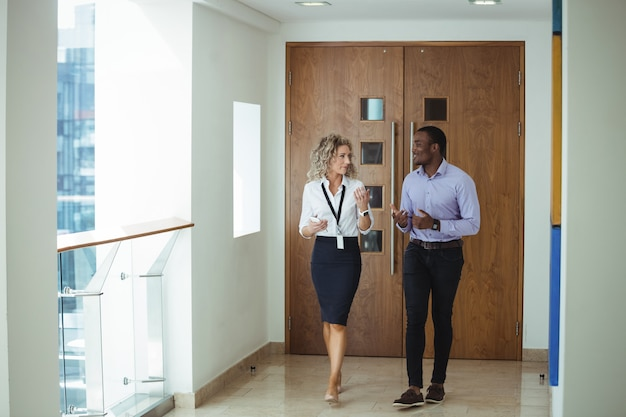 Executivos de negócios, tendo uma discussão enquanto caminhava no corredor