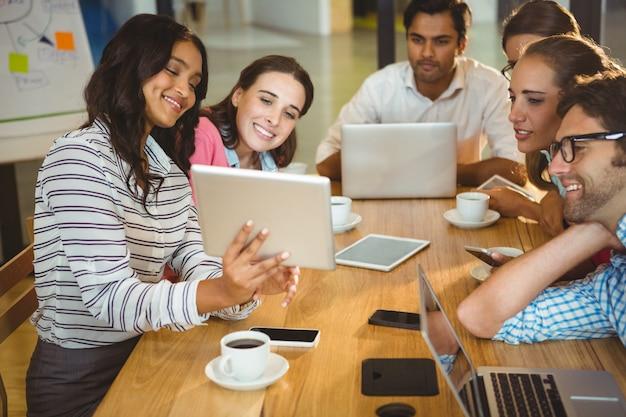 Executivos de negócios usando tablet digital durante reunião