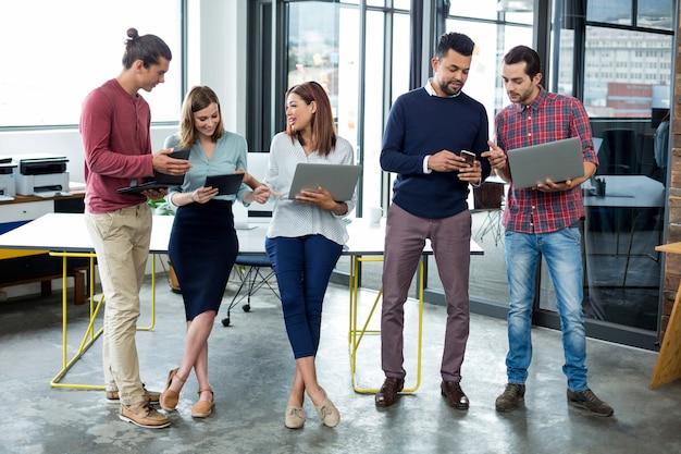 Executivos de negócios usando tablet digital, telefone celular e laptop