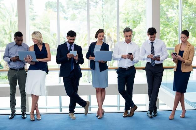 Executivos de negócios usando telefone celular, tablet digital, laptop