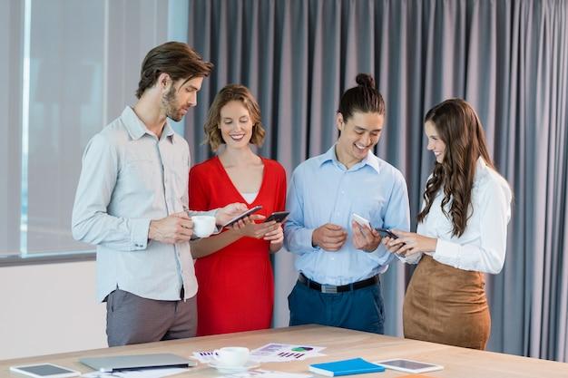 Executivos de negócios usando telefones celulares na sala de conferências