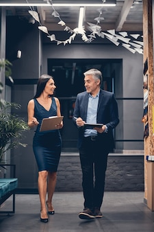 Executivos de retrato vertical caminhando em um escritório moderno enquanto conversam