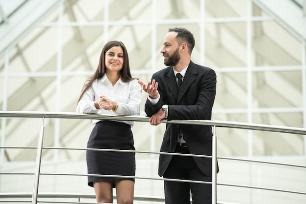 Executivos de sorriso novos no escritório moderno.