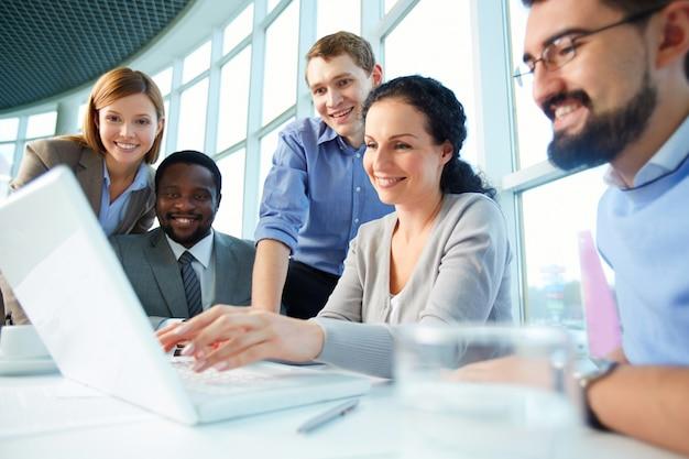 Executivos de sorriso que têm reunião em torno da mesa