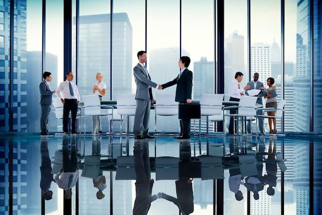 Executivos do conceito da comunicação do aperto de mão da reunião da sala de direção