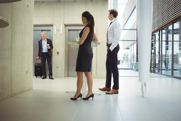 Executivos em pé com copos de água para dar as boas-vindas ao colega