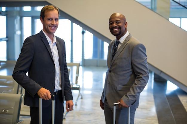 Executivos em pé com uma mala de bagagem no aeroporto