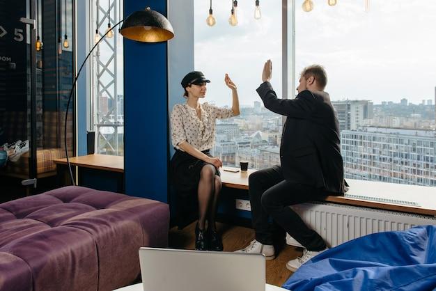 Executivos entusiasmados comemorando a conquista da startup em um escritório moderno